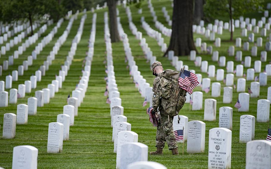 Soldiers place U.S. flags at headstones as part of Flags-In at Arlington National Cemetery, Arlington, Va., on May 21, 2020.