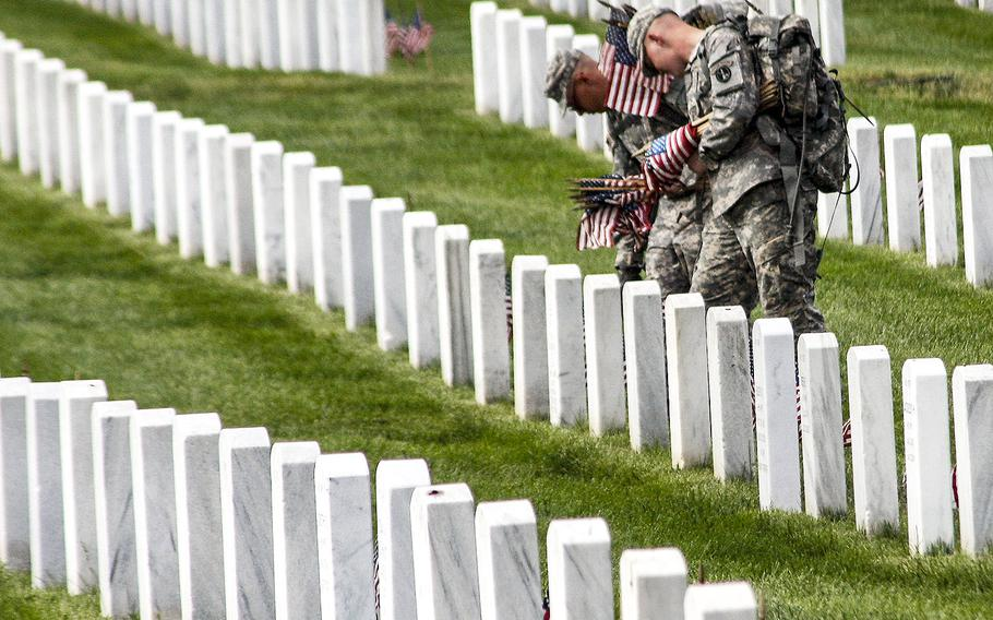 Service members place flags on graves at Arlington National Cemetery before Memorial Day in 2012.