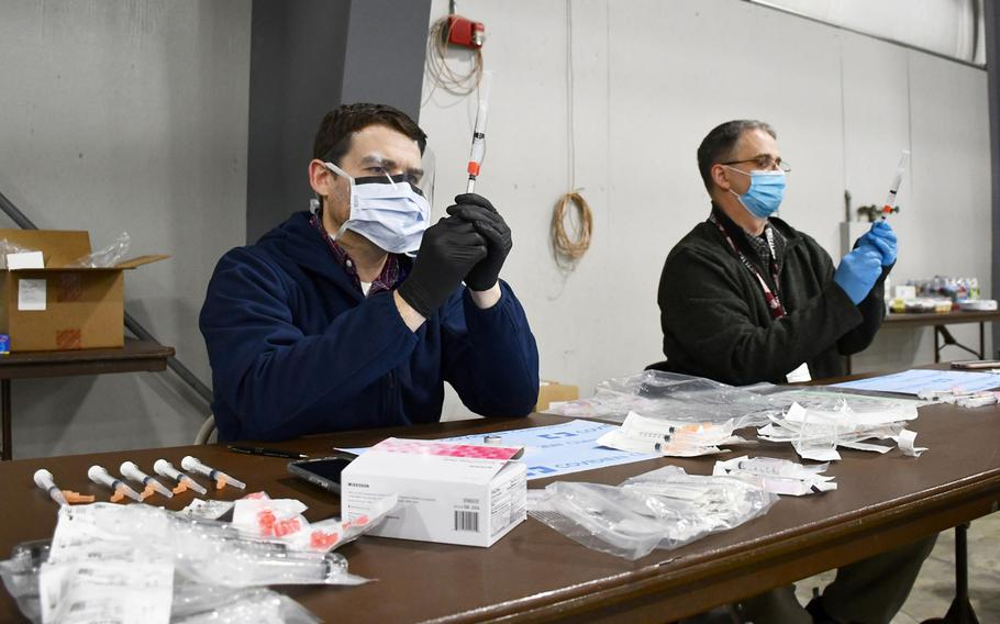 Pharmacists CJ Ludwig, front, and Chris Elizagaray, back, pull doses of the coronavirus vaccine from vials at a Department of Veterans Affairs vaccination clinic on Tuesday, March 2, 2021.