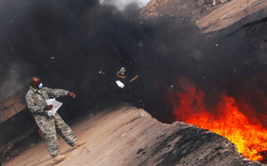 An airman tosses unserviceable uniform items into a burn pit at Balad Air Base, Iraq, on March 10, 2008.