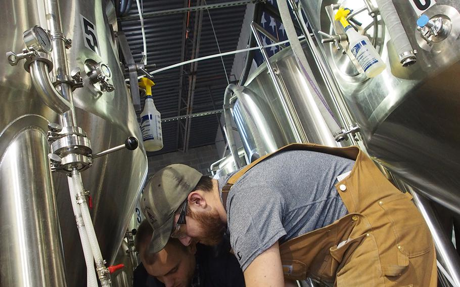 Marine veteran Sean Arroyo, foreground, and Chris Hampel, check equipment at Arroyo???s brewery, Heritage Brewing Co., in Manassas, VA, outside of Washington, DC. The Capital and surrounding area is a hot spot for veteran entrepreneurship.