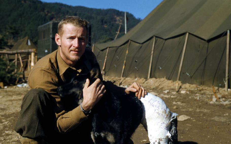 Frank Praytor poses with Mangy, a stray dog he found in 1953 while covering the Korean War as a Marine Corps combat correspondent.
