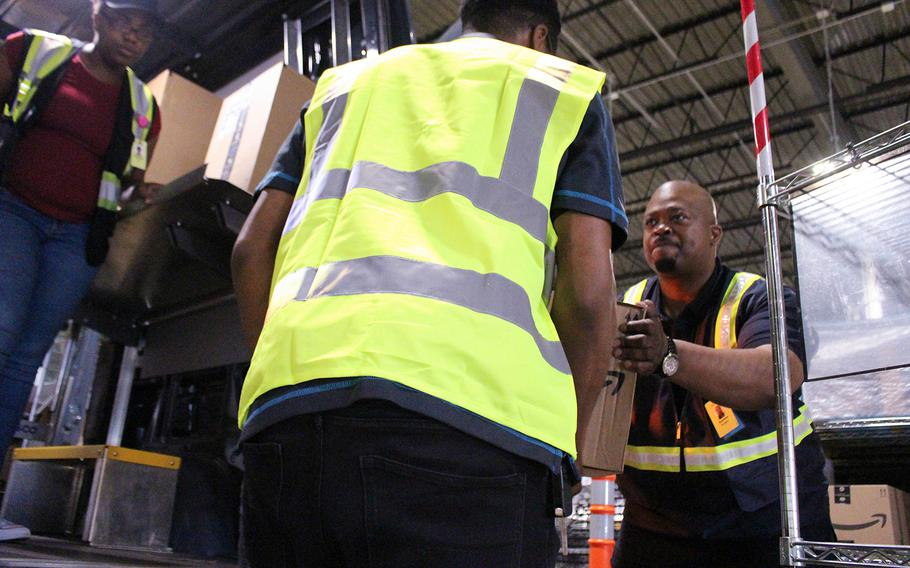 Retired Army Maj. Quinton Burgess (right) helps load items into his truck to be delivered at an Amazon shipping plant in Richmond, Va. Burgess and his Alligiance Logistics LLC company has partnered with Amazon as part of a program that helps veterans become entrepreneurs.