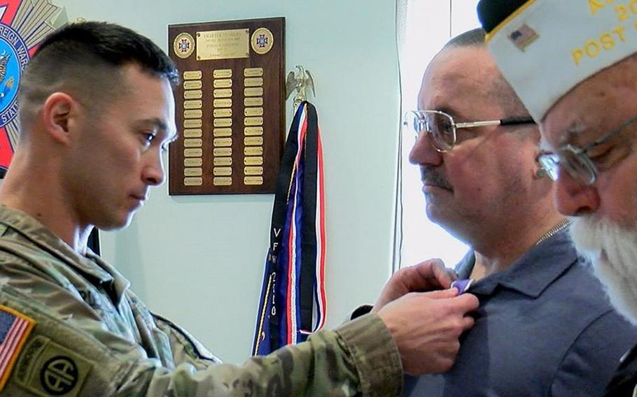 Command Sgt. Maj. Michael Carden of Carlisle Barracks in Pennsylvania pins a Purple Heart onto the lapel of David Ott, a retired National Guard combat medic who was wounded in Iraq in January 2006, as Rick Olson, VFW Post 477 commander, reads the award citation during a luncheon on Wednesday, Jan. 29, 2019.