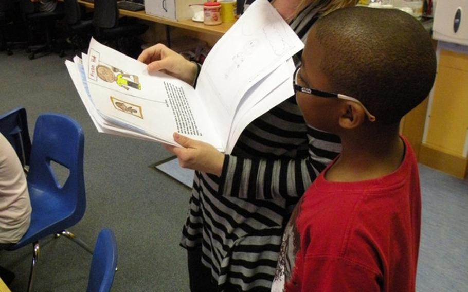 Teacher Karen Griffis reviews the book created by Torence Davis during a work session on March 24 at Feltwell Elementary School. The books were presented to the public at an authors' tea on April 6 and 7.