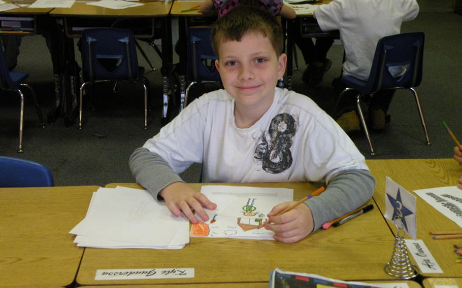 Kyle Gunderson takes a break from coloring a picture he drew while putting together a book about his local hero, Mandy Kumiyama, at Feltwell Elementary School in England. Twenty-two students from Karen Griffis' class held an authors tea, April 6 and 7, to publicly recognize their heroes and read their reports.