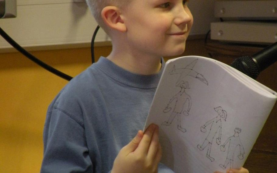 Adam Torkelson pauses from his reading to look over at his hero, his mother Debbie Torkelson, during an authors tea on April 7 in Karen Griffis' class at Feltwell Elementary School. Adam and 21 other students created books about their local heroes for a project that Griffis also organized in classrooms in Japan and the United States.