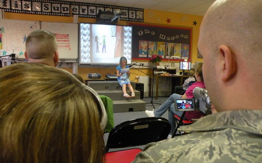 Alexis Kimes reads a story about her hero and father, Master Sgt. Gary Kimes  of the 351st Air Refueling Squadron at RAF Mildenhall, England, during an authors tea on April 7 in teacher Karen Griffis' class at Feltwell Elementary School.