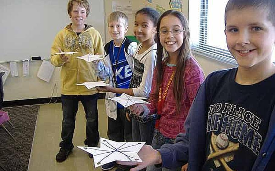 From left, fifth-graders Max Taber, Dylan Herron, Serena Johnson, Kathiana McIntyre and Sam Terry pose for a picture while balancing stars on their fingers during an exercise about finding the center of balance in January at Kinser Elementary School on Okinawa. It was one of several mini-experiments their teacher Laurie Arensdorf arranged while the class built a game for NASA's 'Spaced Out Sports' contest. The fifth-graders finished second in the competition.
